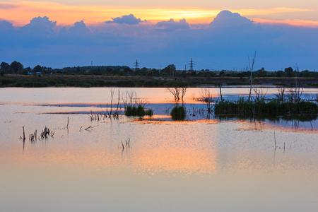 Sunset summer lake landscape with sun reflection on water surface (near Shklo settlement, Lviv Oblast, Ukraine).