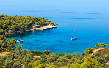 Morning summer Aegean Sea coast with pine trees on shore and small yachts in bay (Sithonia, Halkidiki, Greece). People unrecognizable. Stock Photo