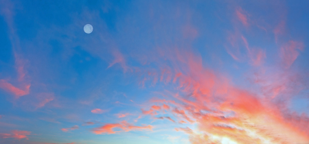 Evening sunset sky with red clouds and fool moon. Good for sky background.