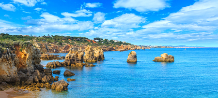 Summer Atlantic coast landscape with rock formations near beach Praia dos Arrifes, Albufeira, Algarve, Portugal. Three shots stitch panorama. 版權商用圖片