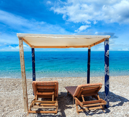 Summer morning beach with aquamarine water and sunbeds (Albania). Two shots stitch high resolution image.