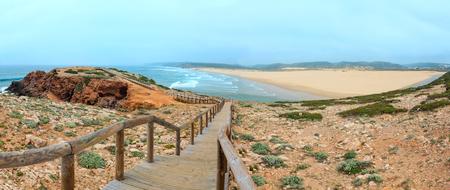 Summer Atlantic coast and lookout point at sandy beach Praia da Bordeira near river estuary. Misty view (Carrapateira, Algarve, Portugal). Two shots stitch panorama.