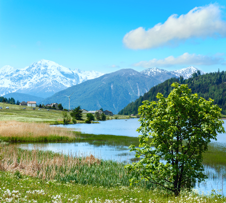 dandelion snow: Summer mountain landscape with lake Lago di Resia and blue cloudy sky (Italy). Two shots stitch image.
