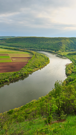 Top picturesque view of the Dnister river bend canyon, with spring fields on coast. Ternopil region, Ukraine, Europe. Stock Photo