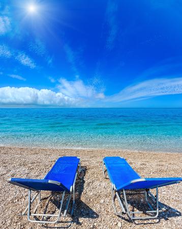 Summer sunshiny beach with sunbeds, white pebble and aquamarine water (Albania). Two shots stitch image. Stock Photo