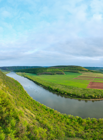 Evening top picturesque view of the Dnister river bend canyon, with spring fields on coast. Ternopil region, Ukraine, Europe. Two shots stitch image.