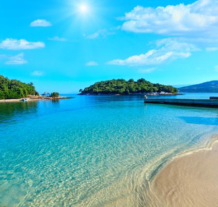 Prachtige Ionische zee met helder turquoise water en ochtendzomer kust sunshiny uitzicht vanaf het strand (Ksamil, Albanië). Mensen onherkenbaar.