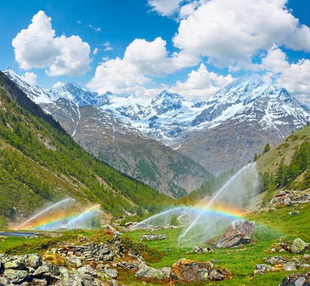 Rainbows in irrigation water spouts in Summer Alps mountain (Switzerland, near Zermatt). Two shots stitch image. Stock Photo