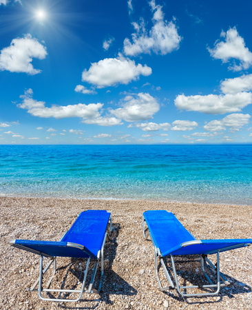 Summer morning sunshiny beach with sunbeds, white sand and pebble (Albania). Two shots stitch high resolution image.