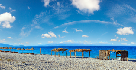 Summer morning beach with sunbeds, canopies and white pebble (Borsh, Albania). Deep blue sky with some clouds.  Three shots stitch panorama.