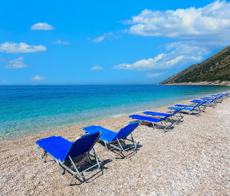 Summer morning pebbly beach with sunbeds (Albania). Two shots stitch image.