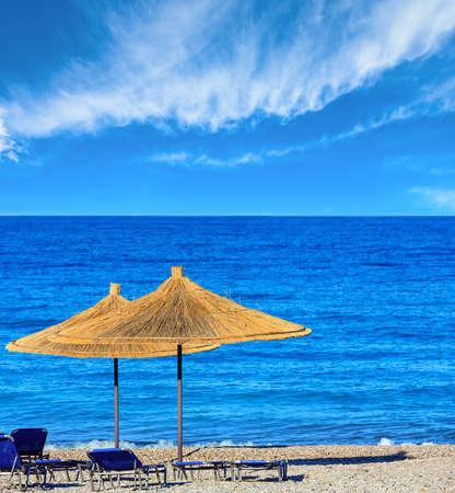 Summer morning pebbly beach with sunbeds and strawy sunshades (Borsh, Albania). Blue sky with some clouds. Stock Photo