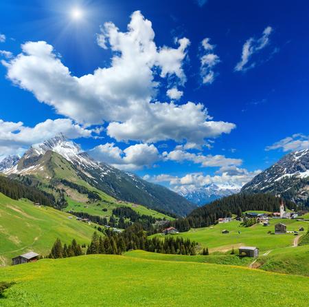 Summer mountain  sunshiny view to Biberkopf mount (Warth, Vorarlberg, Austria) and deep blue sky with clouds. Stock Photo
