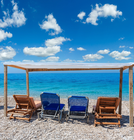 Summer morning beach with aquamarine water, blue sky and sunbeds (Albania). Two shots stitch image. Stock Photo