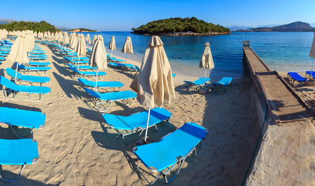 Summer morning sandy Ksamil Beach with sunbeds and sunshades (Albania). Two shots stitch panorama. Stock Photo