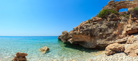 Hole in rock on Drymades beach, Albania. Summer Ionian sea coast view. Two shots stitch panorama.