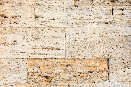 spongy: Fragment of a stone wall made of limestone bricks with spongy surface (architectural background pattern). Stock Photo