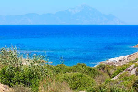 Summer stony sea coast landscape with Atthos mount view in far(Halkidiki, Sithonia, Greece).