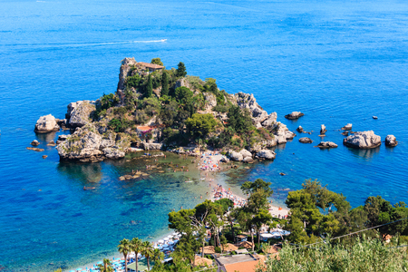 Taormina Isola Bella beach and Isola Bella islet view from up, Sicily, Italy. Summer Sicilian seascape with sea coast, beaches and island. People unrecognizable (people specially some blurred).
