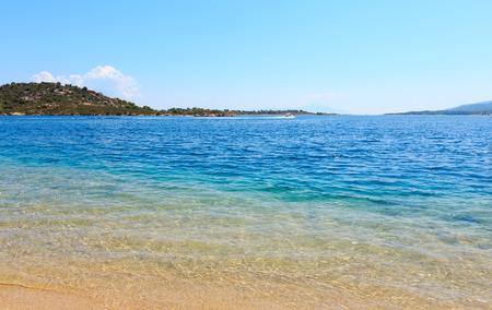 Summer Aegean sea coast landscape (Livari beach, Halkidiki, Sithonia, Greece). People are unrecognizable.