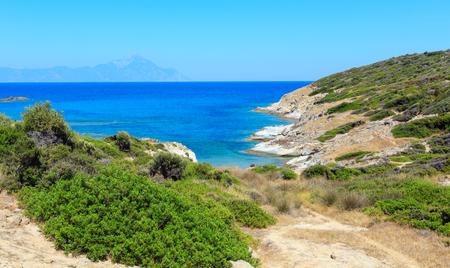 Summer stony sea coast landscape with Atthos mount view in far(Halkidiki, Sithonia, Greece).