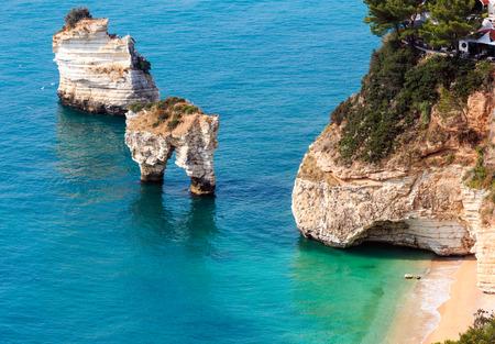 Picturesque islets Faraglioni di Puglia in summer Adriatic sea bay Baia Delle Zagare (Mattinata, Gargano peninsula, Puglia, Italy)