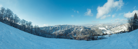 The first shadows of setting sun on winter mountain slopes with ski run and surface lift (Skole, Lviv Oblast, Carpathians, Ukraine).Three shots stitch  high-resolution panorama.  People are unrecognizable. Stock Photo