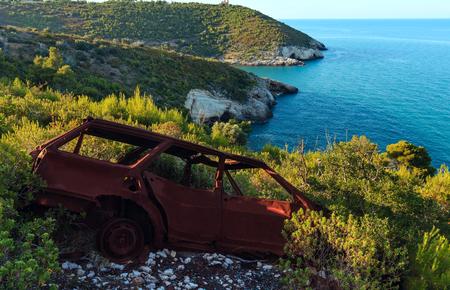 rusty car: Broken demage rusty car on summer sea coast hill near Arch of San Felice on the Gargano peninsula in Puglia, Italy