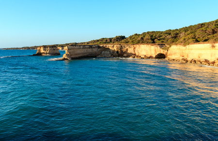 Picturesque sunrise seascape with white rocky cliffs, sea bay, islets and faraglioni at beach Spiaggia della Punticeddha, Salento Adriatic sea coast, Puglia, Italy.