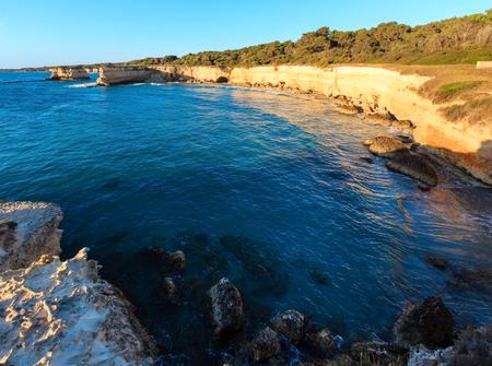 Picturesque sunrise seascape with white rocky cliffs, sea bay, islets and faraglioni at beach Spiaggia della Punticeddha, Salento Adriatic sea coast, Puglia, Italy