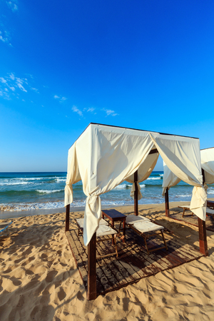 Luxury beach tents canopies on morning paradise white sandy beach The Maldives of Salento (Pescoluse, Salento, Puglia, south Italy). The most beautiful sea sandy beach of Apulia.