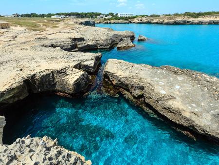 Picturesque seascape with white rocky cliffs, caves, sea bay and islets at Grotta della poesia, Roca Vecchia, Salento Adriatic sea coast, Puglia, Italy Stock Photo
