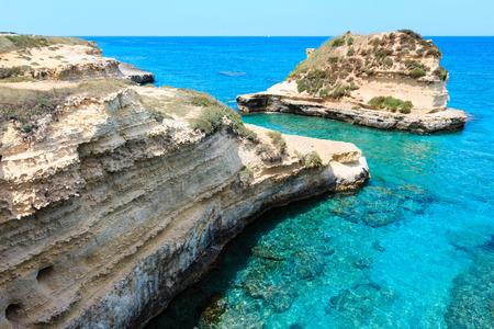 Picturesque seascape with white rocky cliffs, sea bay and islets at Grotta dello Mbruficu, Salento Adriatic sea coast, Puglia, Italy