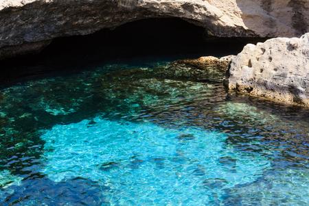 Picturesque seascape with white rocky cliffs, caves, sea bay and islets at Grotta della poesia, Roca Vecchia, Salento Adriatic sea coast, Puglia, Italy Фото со стока
