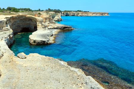 Picturesque seascape with white rocky cliffs, caves, sea bay and islets at Grotta del Canale, SantAndrea, Salento Adriatic sea coast, Puglia, Italy