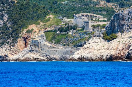 Beautiful medieval fisherman town of Portovenere (UNESCO Heritage Site) view from sea (near Cinque Terre, Liguria, Italy). Fortress Castello Doria and church Chiesa di San Pietro.