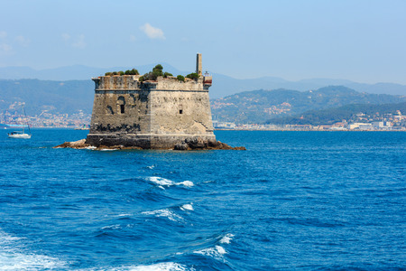 Scola Tower (tower of St. John the Baptist) - is a former military building just near Palmaria island in Portovenere, in the Gulf of Poets (La Spezia, Liguria, Italy). View from excursian ship. People unrecognizable. Stock Photo