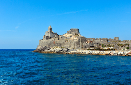 Medieval fisherman town of Portovenere (UNESCO Heritage Site) view from sea (near Cinque Terre, Liguria, Italy). Fortress Castello Doria and church Chiesa di San Pietro (build in 13th century).