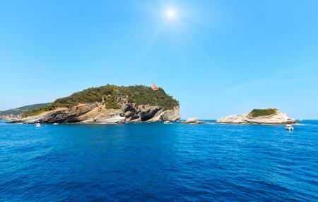Sunshiny rocky sea coast of Palmaria, Tino and Tinetto islands near Portovenere (Gulf of Poets, Cinque Terre National Park, La Spezia, Liguria, Italy). Lighthouse on Tino island. 写真素材