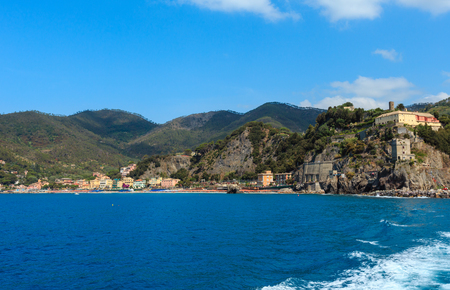 Summer Monterosso view from excursion ship. One of five famous villages of Cinque Terre National Park in Liguria, Italy, suspended between Ligurian sea and land on sheer cliffs. People unrecognizable. 版權商用圖片