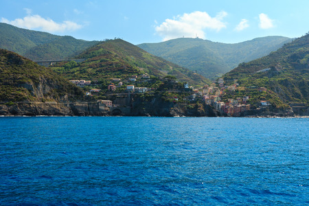 Summer Manarola view from excursion ship. One of five famous villages of Cinque Terre National Park in Liguria, Italy, suspended between Ligurian sea and land on sheer cliffs. People unrecognizable. 版權商用圖片