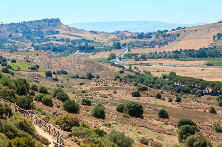 View to road, gardens and mountain from famous ancient ruins in Valley of Temples, Agrigento, Sicily, Italy.