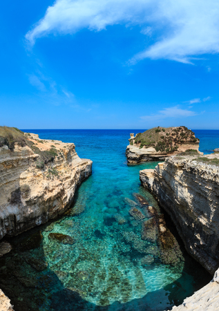 Picturesque seascape with white rocky cliffs, sea bay and islets at Grotta dello Mbruficu, Salento Adriatic sea coast, Puglia, Italy
