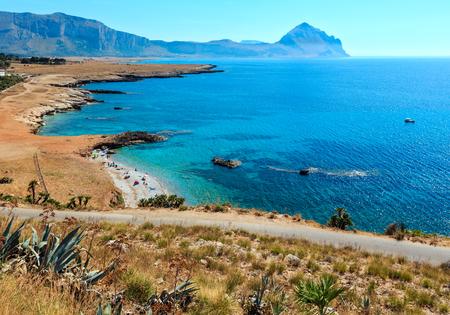 Azure Tyrrhenian sea picturesque bay, Monte Cofano mount and Bue Marino Beach view, Macari, San Vito Lo Capo region, Sicily, Italy. People are unrecognizable.