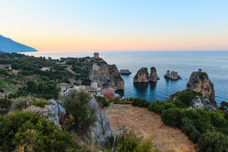 Evening twilight view of beautiful Tyrrhenian sea bay and the Faraglioni di Scopello from above, Province of Trapani, Sicily, Italy. Stock Photo