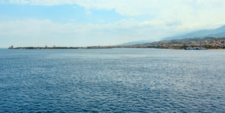 View of the Messina sea strait and coastline from the side of the ferry to Sicily island, Italy. Villa San Giovanni town on shore.