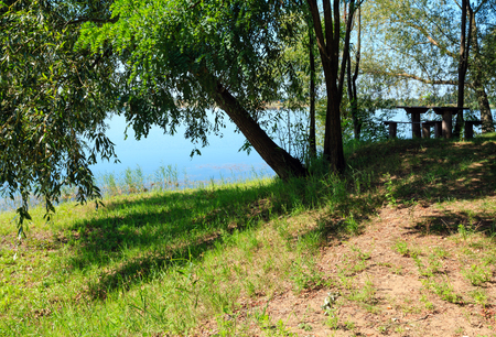 Picturesque summer lake calm landscape with camping pitch on shore. Concept of tranquil country life, eco friendly tourism, camping, fishing.