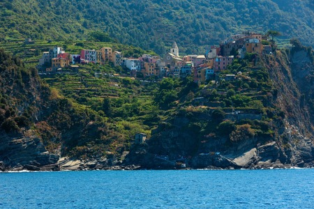Summer Corniglia view from excursion ship. One of five famous villages of Cinque Terre National Park in Liguria, Italy, suspended between sea and land on sheer cliffs. People unrecognizable. Stock Photo