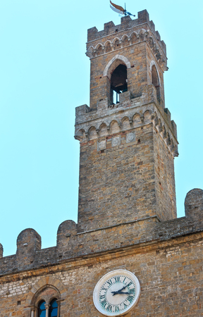 Palazzo dei Priori tower top in ancient walled mountaintop town Volterra, construction finished in 1257, Pisa province, Tuscany, Italy.