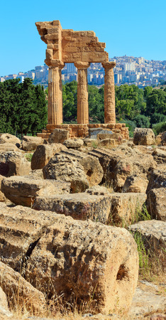 Temple of Dioscuri (Castor and Pollux) with Agrigento town in the background. Famous ancient ruins in Valley of Temples, Agrigento, Sicily, Italy. Three shots high-resolution composite image. Editorial